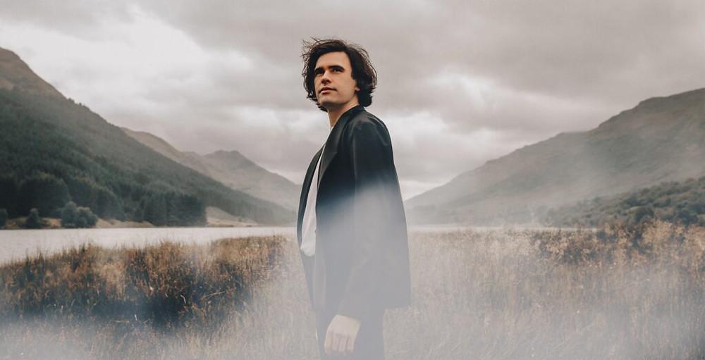 Scott Sylvan stands in a field in Scotland