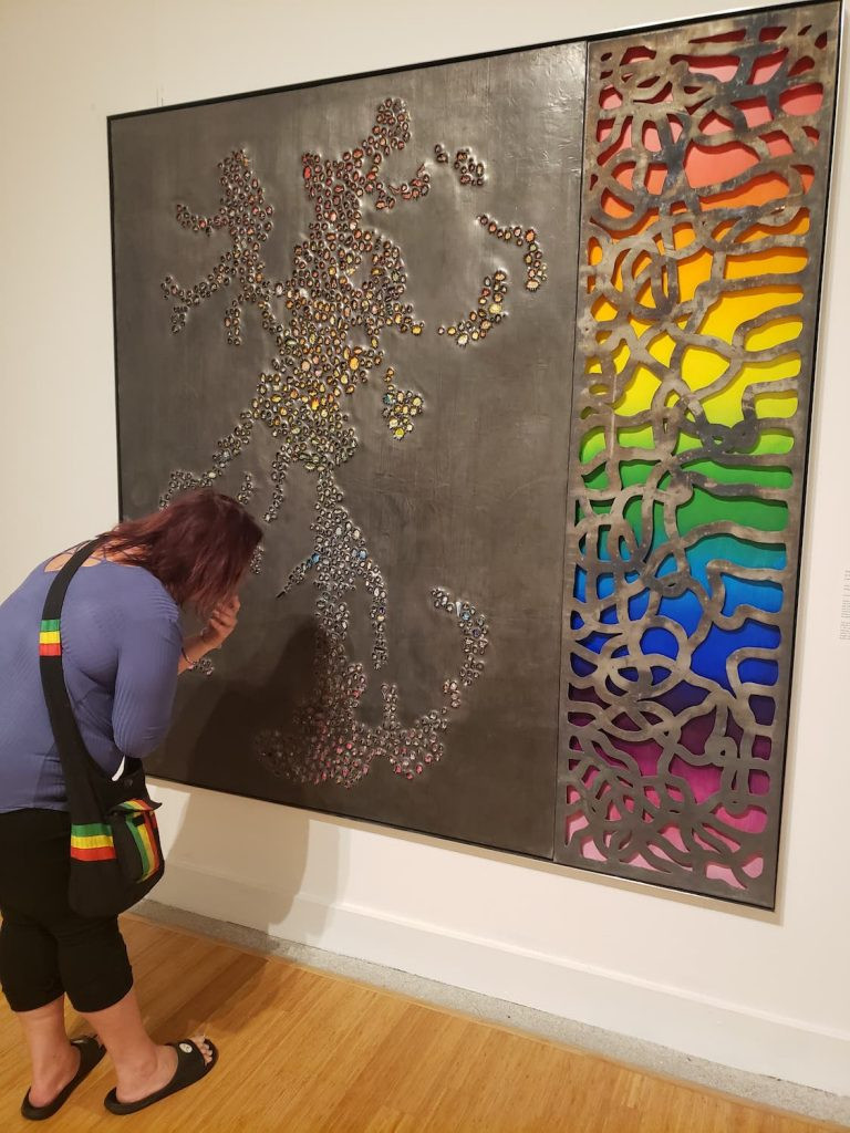 Carlos Vega, Just Discovered- a rainbow background is hidden by a metal top with patterns and holes in it where the rainbow shows though. A woman bends over to see a portion of the piece closer.