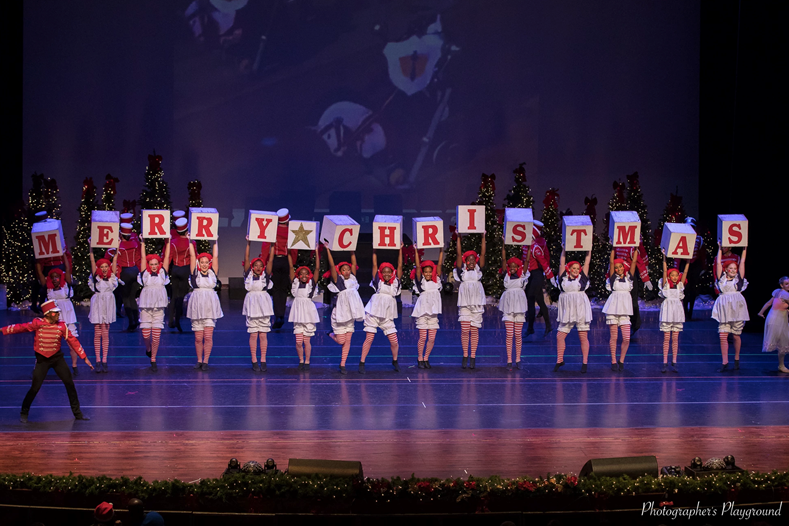 "Young dancers at the Academy's Christmas recital, they hold up blocks that read ""Merry Christmas"""