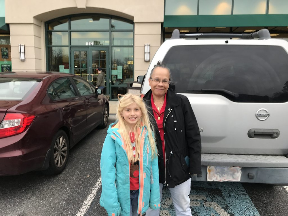 Gloria and her daughter pose for a picture in a parking lot