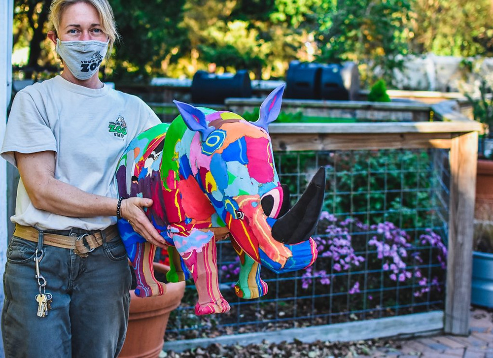 Virginia Zoo Keeper stands with a rhino flip flop animal, an item available in the Zoo's Virtual Auction. The auction runs November 9 to 20 and benefits the Zoo's Emergency Operating Fund.