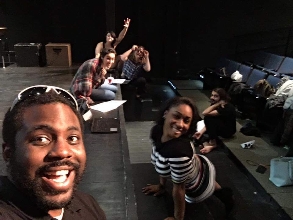 Moriah and friends are in a theater sitting on the edge of the stage rehearsing for a play