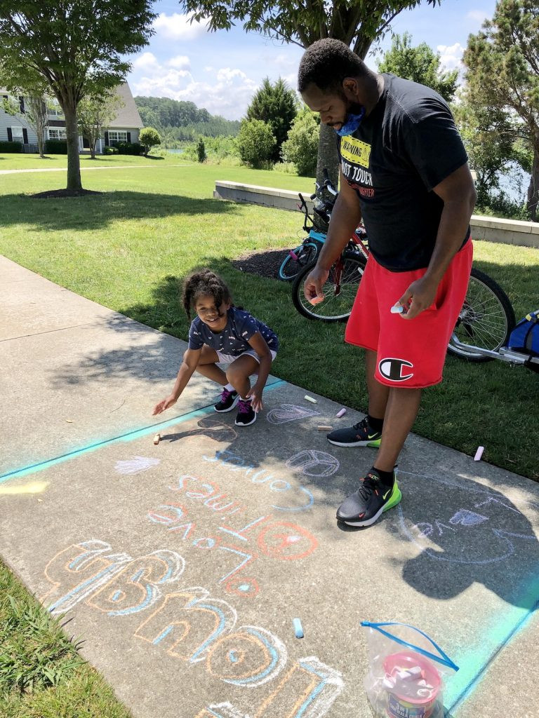 A dad helps his daughter with sidewalk art. Their chalk reads Tough: love, times, convos.