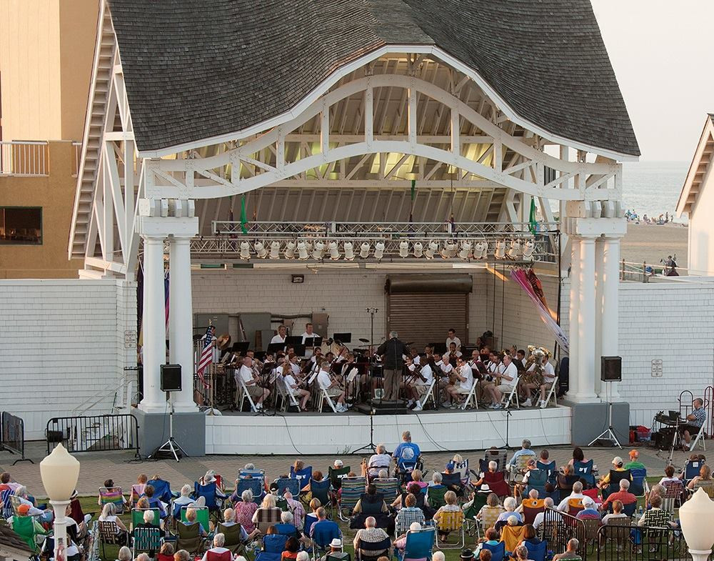 Tidewater winds plays at an outdoor venue, the stage from far away with some crowd in front