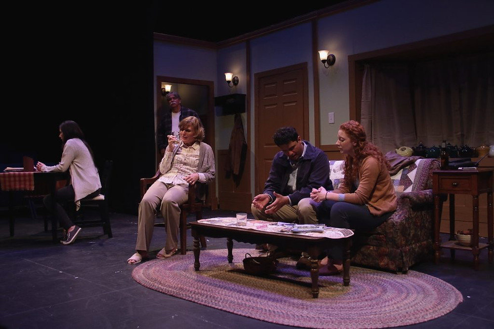 Photo from The Resting Place at the Goode Theater, the set is a living room, the family sits around in grief, drinking. They do not look at each other.