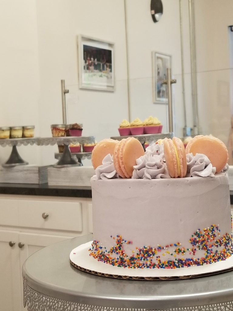 a pink cake with macrons on top