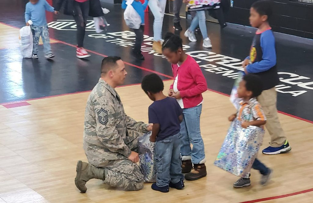 A member of the Virginia National Air Guard talking to some children at a Kids Wish List event