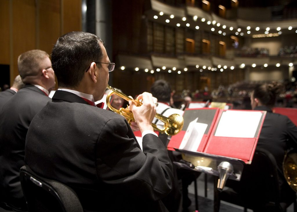 The view from over the shoulder of a trumpet player. We see his music and some of the audience.