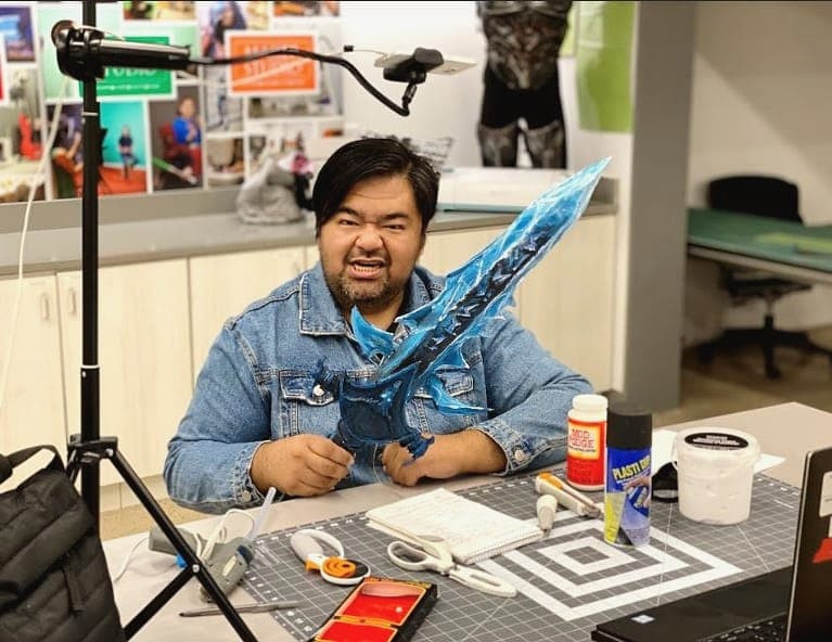 Philip Odango sits at a workbench surrounded by tools and materials, holding up his ice sword