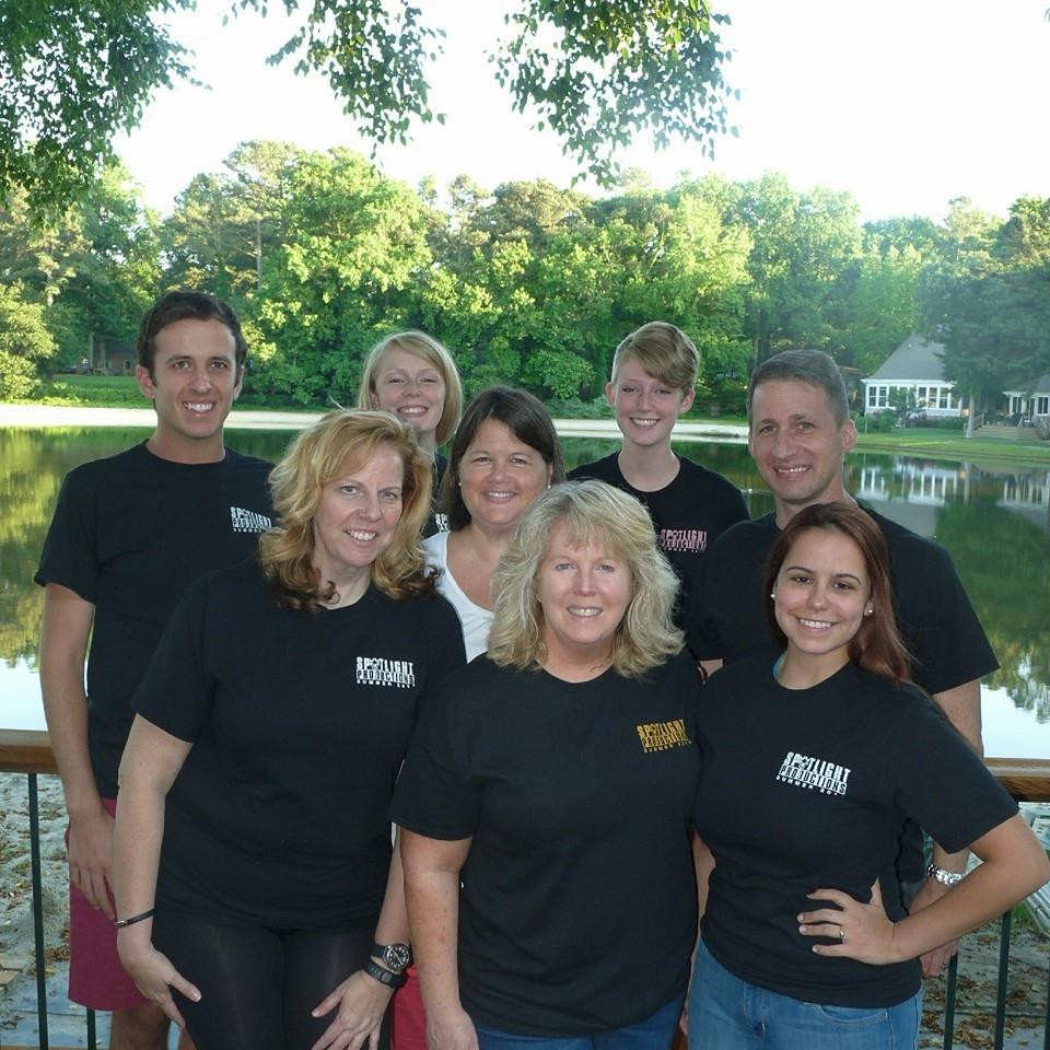 The staff of Spotlight Productions in matching shirts by a lake