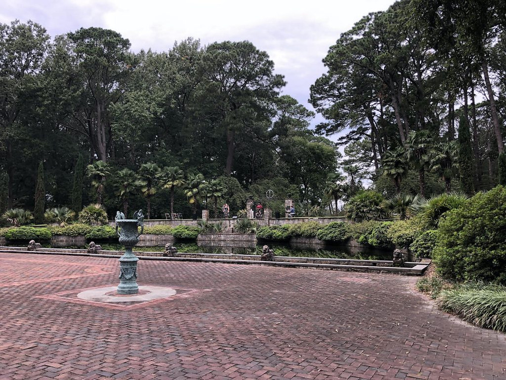 The botanical gardens, a statue in the middle of a brick walkway, bushes and plants surrounding it.