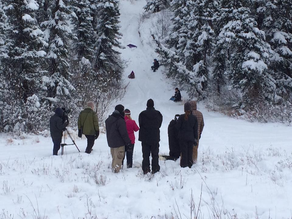 A group of people with sleds appear to have wiped out on a snowy hill. In the foreground, a film crew can be seen working.
