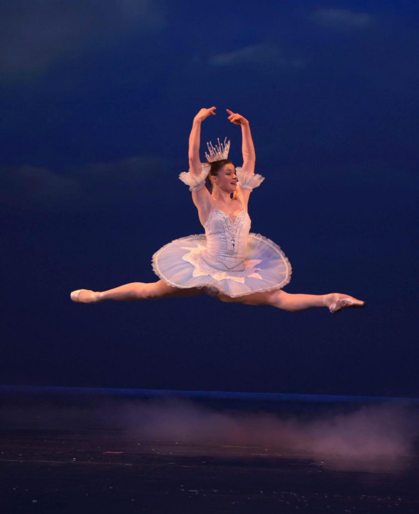 A ballerina leaps through the air on stage