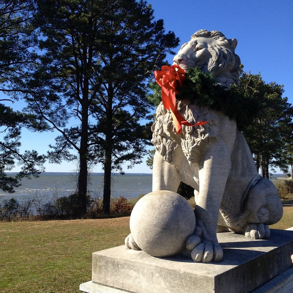 Statue of a lion at the trailhead of the Noland trail. it is wearing a wreath as a necklace.
