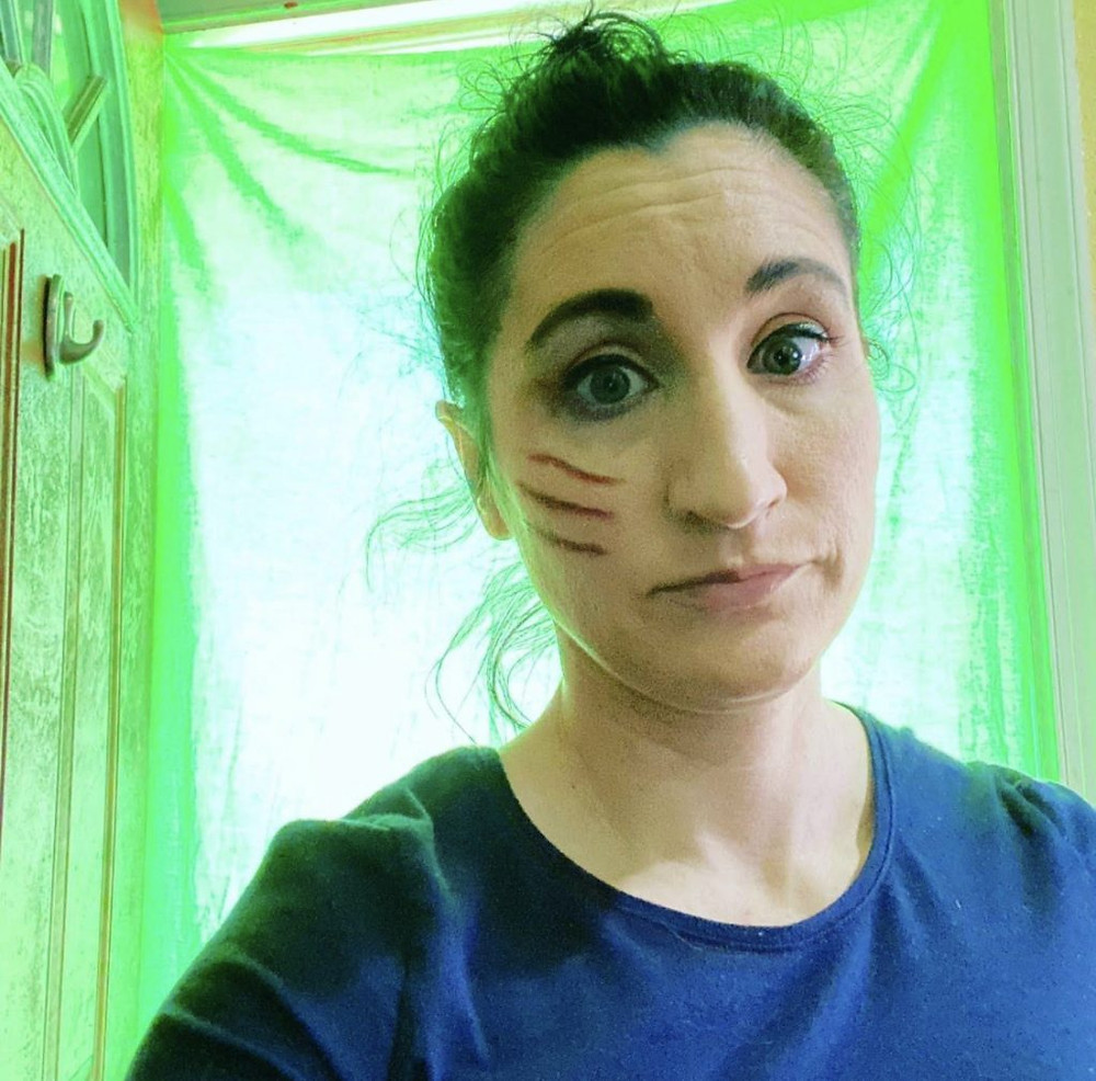 Anna Tozzi Barbay with 3 make up cuts on her face in front of a lit up green curtain.