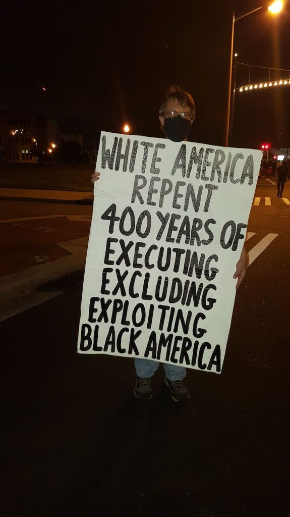 "A white man holds a sign that says ""White America Repent. 400 years of executing, excluding, exploiting black America."""
