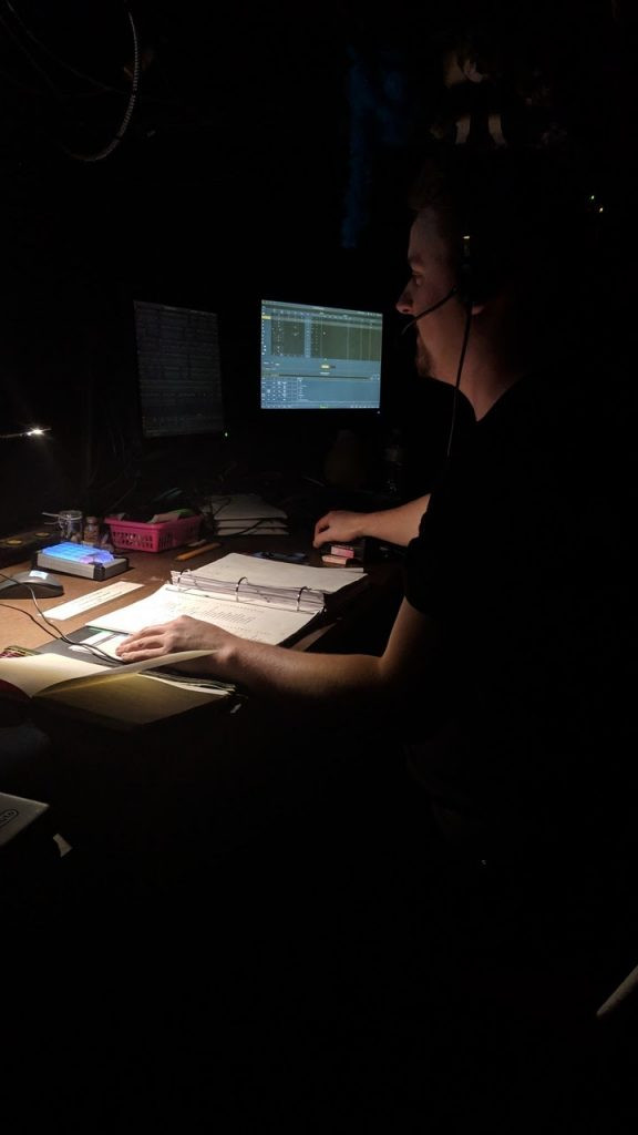 Ryan sits behind a dark desk in Toronto wearing a headset as a stage manager.