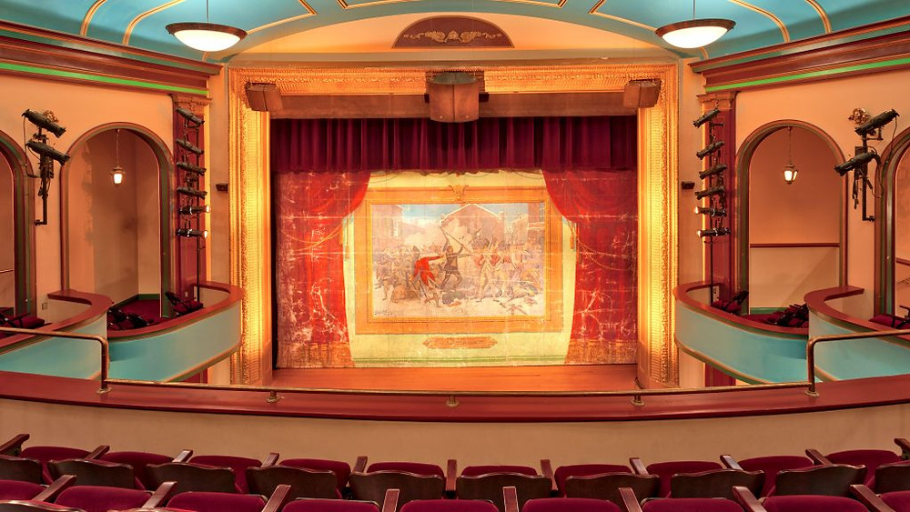 A photo of the restored fire curtain, painted with a beautiful picture of a revolutionary war battle.