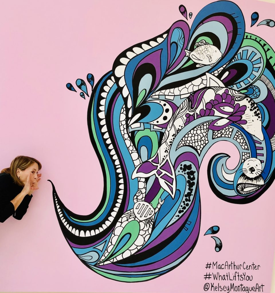 A woman leaning into a pink background. It looks like she is blowing out air or possibly shouting. On the pink background is a swirl of colors, blue and purple and white and black and green, which appear to have come out of her mouth. #MacArthurCenter #WhatLiftsYou @KelseyMontagueArt