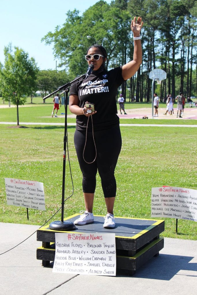 Ashley Houston speaks at the mic with her hand in the air