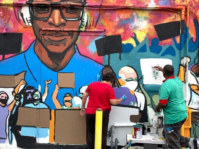 Painters working on the mural at ground level.