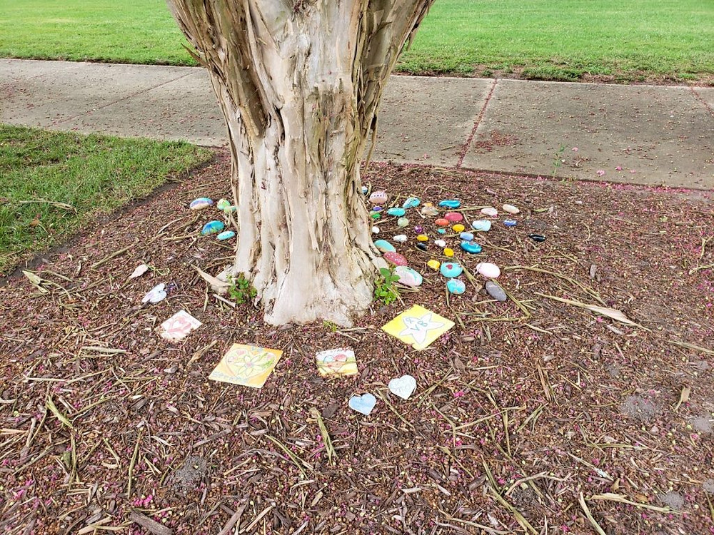 Painted rocks and tiles displayed around the base of a tree.