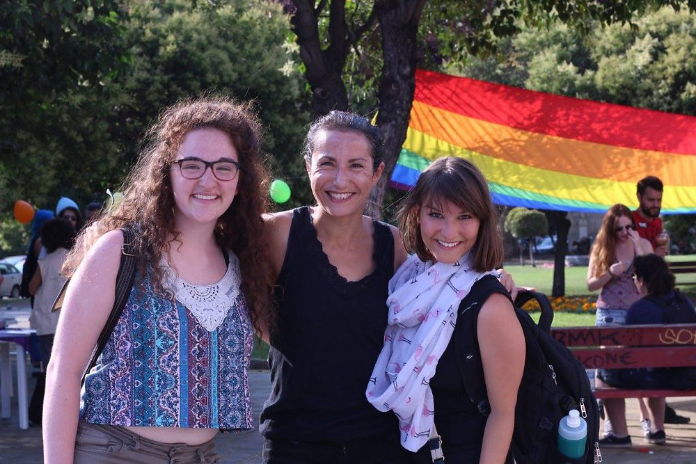 Joanna with friends in Greece at a pride fest, a rainbow flag is stretched between trees in the background.