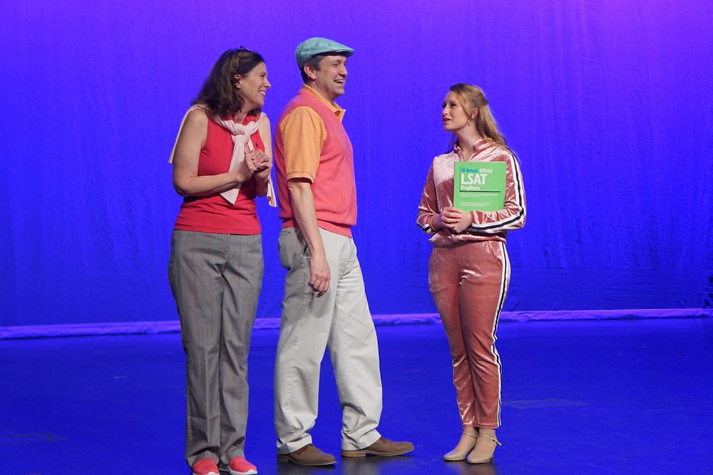 Dr. Sally Shedd, Dr. Travis Malone, and student Abby Horgan in Legally Blonde- they are onstage in costumes with a blue background.