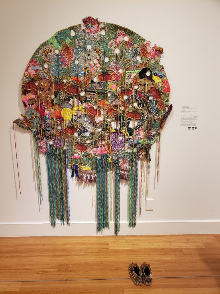 Ebony G Patterson's work He- a large circle with many different colored fabrics and beads hanging off of it.