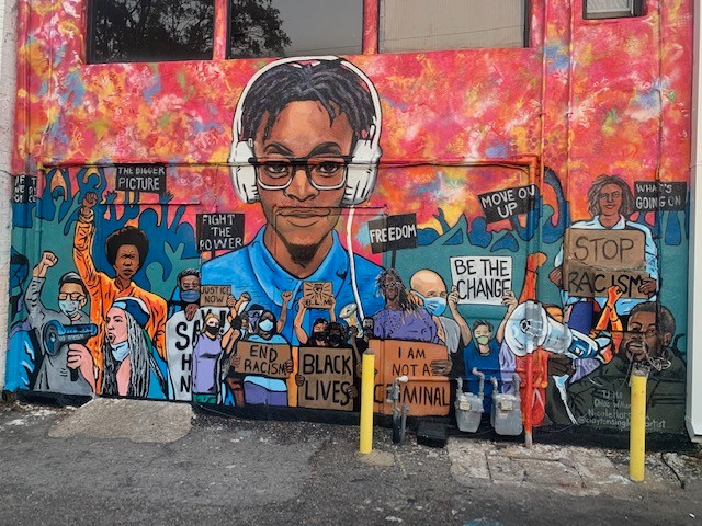 The completed mural, with no one in the way. A black boy with headphones is the centerpiece. He looks out at us. Surrounding him are many other people of all colors, some holding signs, some bullhorns, some wear masks, some have their fists in the air. This is all imposed on a warm colored abstract background. Behind the clearer people are silhouettes of even more people, turning the whole picture into a march.