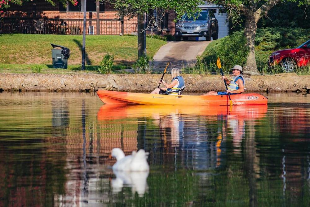 A man and a woman having fun using a tandem kayak
