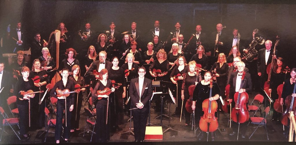 A group shot of the Hampton Roads Philharmonic. They are standing on stage with their instruments.