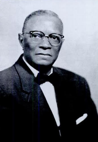 A black and white portrait of Harvey Johnson. He is older, wearing glasses, and looking at the camera with a serious but kind expression.