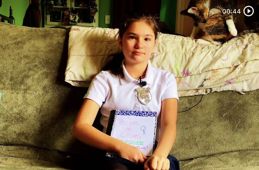 Anna's daughter sits on the couch with a notebook during their 48 hour in quarantine project.