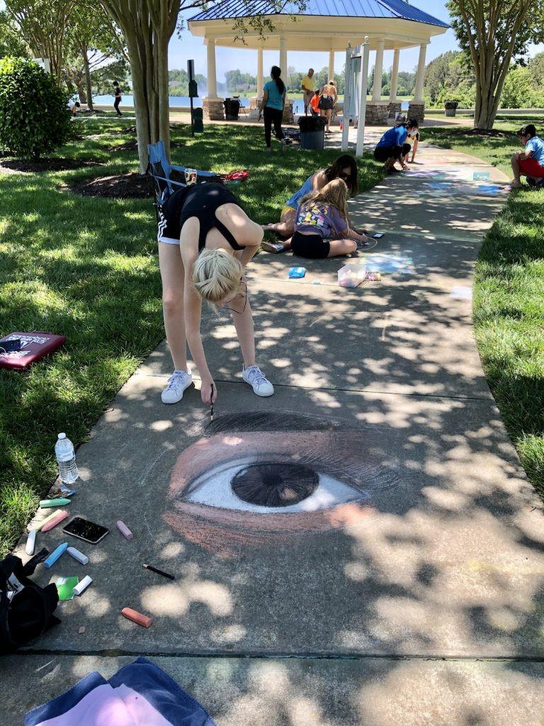 A sidewalk artist draws an eye