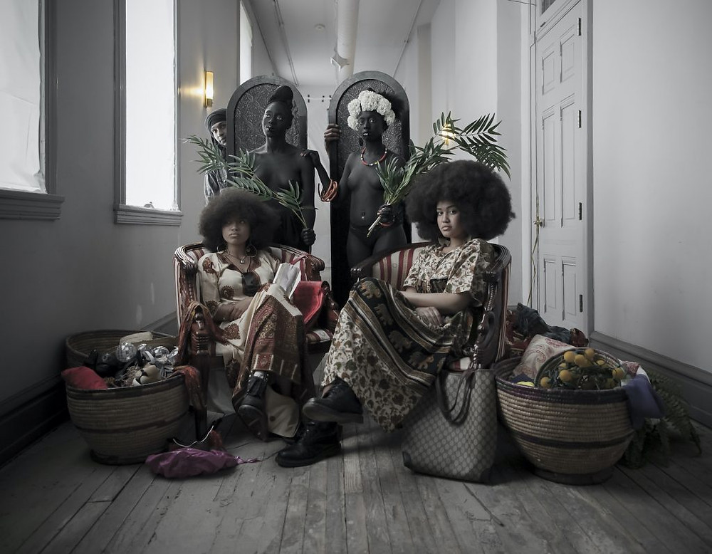 Two ladies in off white and brown dresses sit in chairs, their hair naturally in giant afros, surrounded by bags and two black statues of naked women, with two other women looking out from around large black arches in the back.