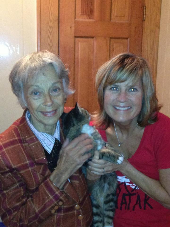 Two women holding a cat who is looking away.