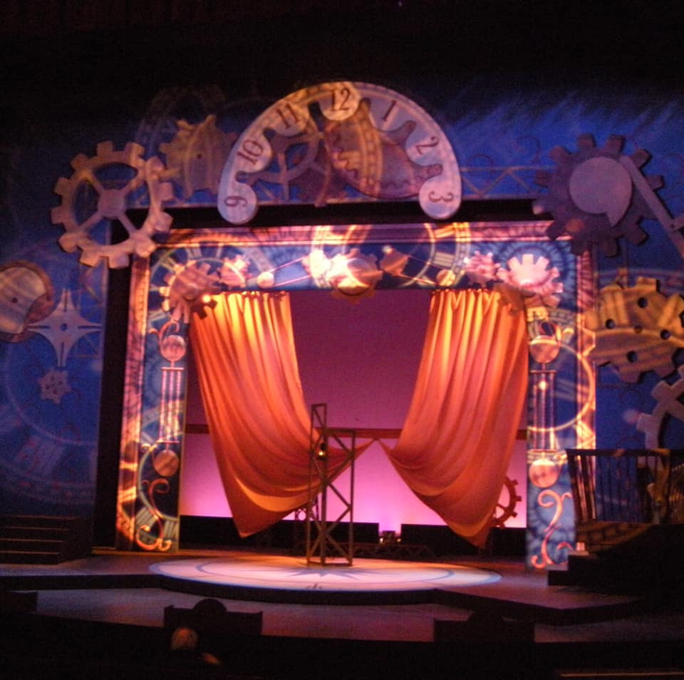 A photo of the Around the World in 80 Days set from the Virginia Stage Company. Lots of clock pieces, a blue false proscenium with a gold curtain.