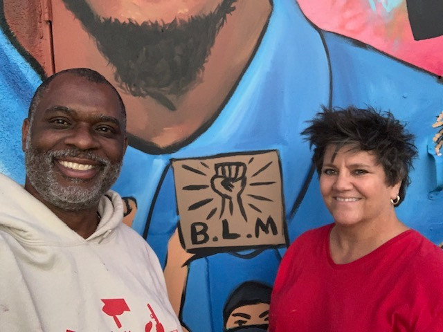 Clayton and Nicole pose in front of a portion of their mural that reads B.L.M.