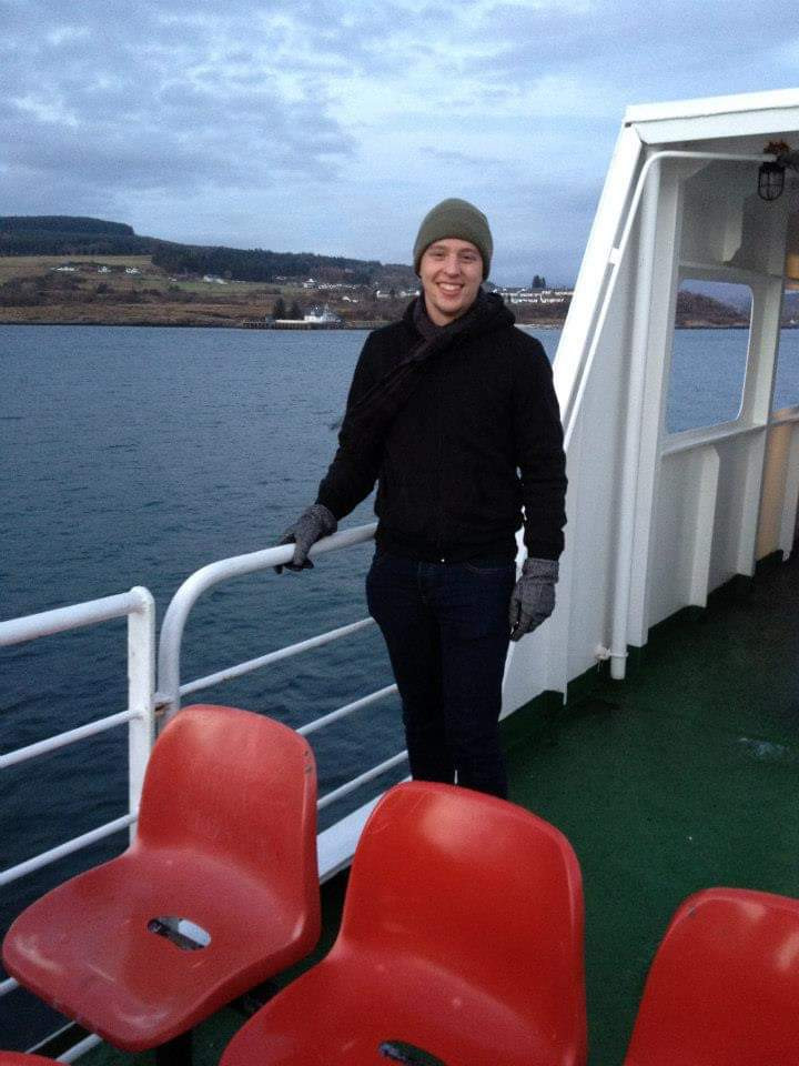 Ryan stands on a boat in Scotland wearing long sleeves, a winter hat, and gloves.