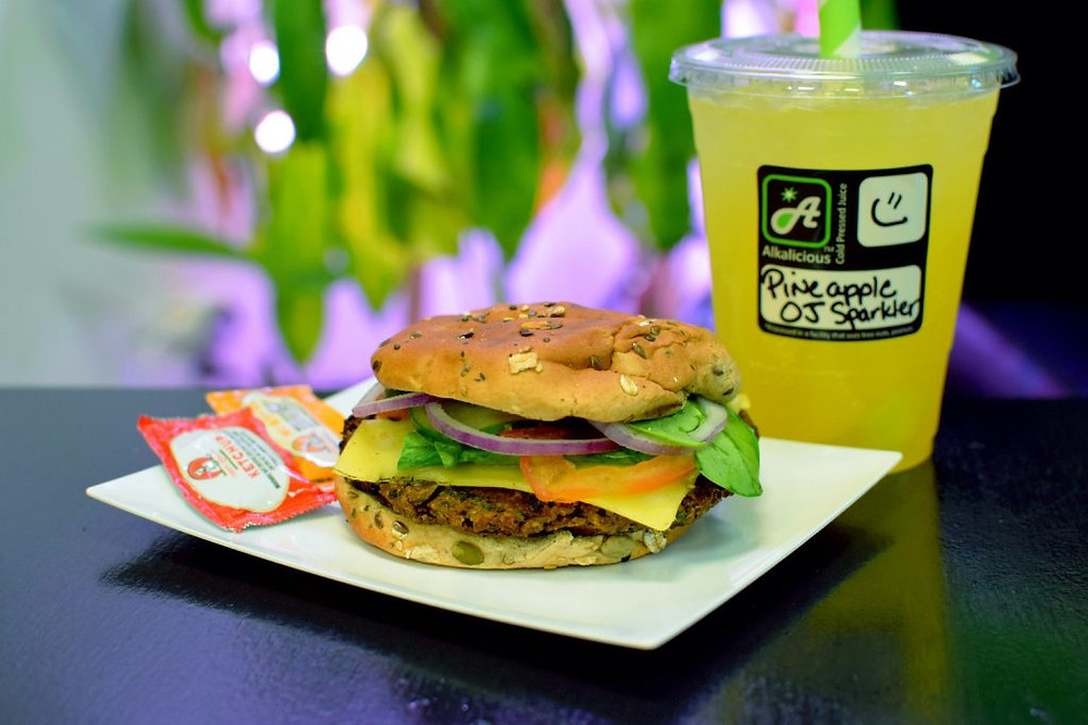 Their black bean burger with cheese, lettuce, and onion and a pineapple and orange juice drink
