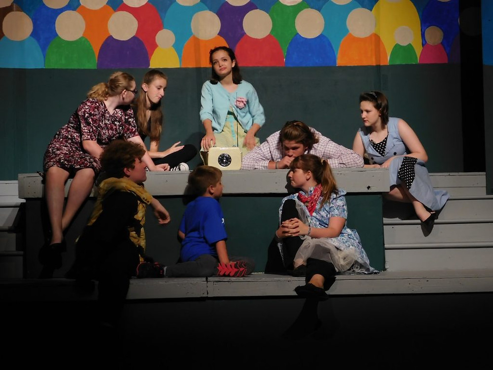 A variety of kids lounging on platforms during their production of Damn Yankees