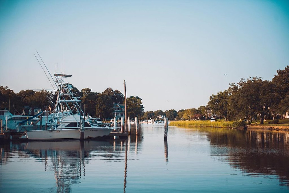 A peaceful section of the Lafayette river, with larger boats parked on the left side.