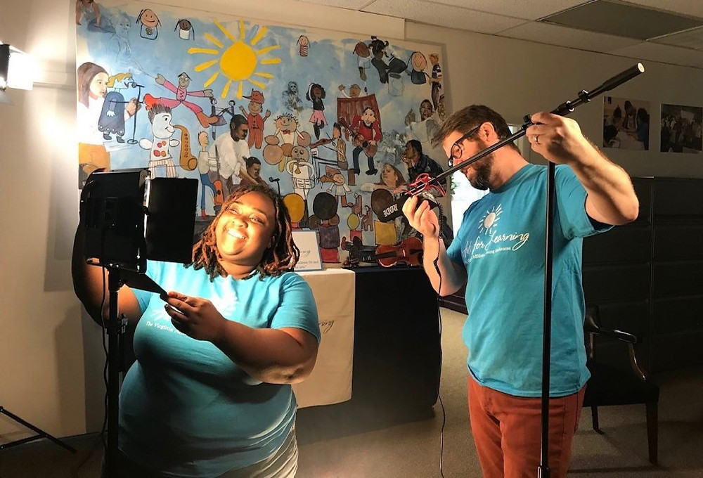 Aaron Kirkpatrick and Aisha Noel set up for a Take 10 segment by placing microphones and lights in their space.