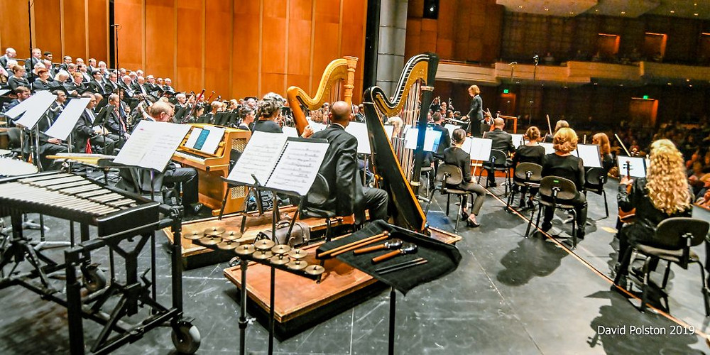 A picture from onstage at the Symphony, with percussion instruments on stands in the foreground, and harps and string players in the background.
