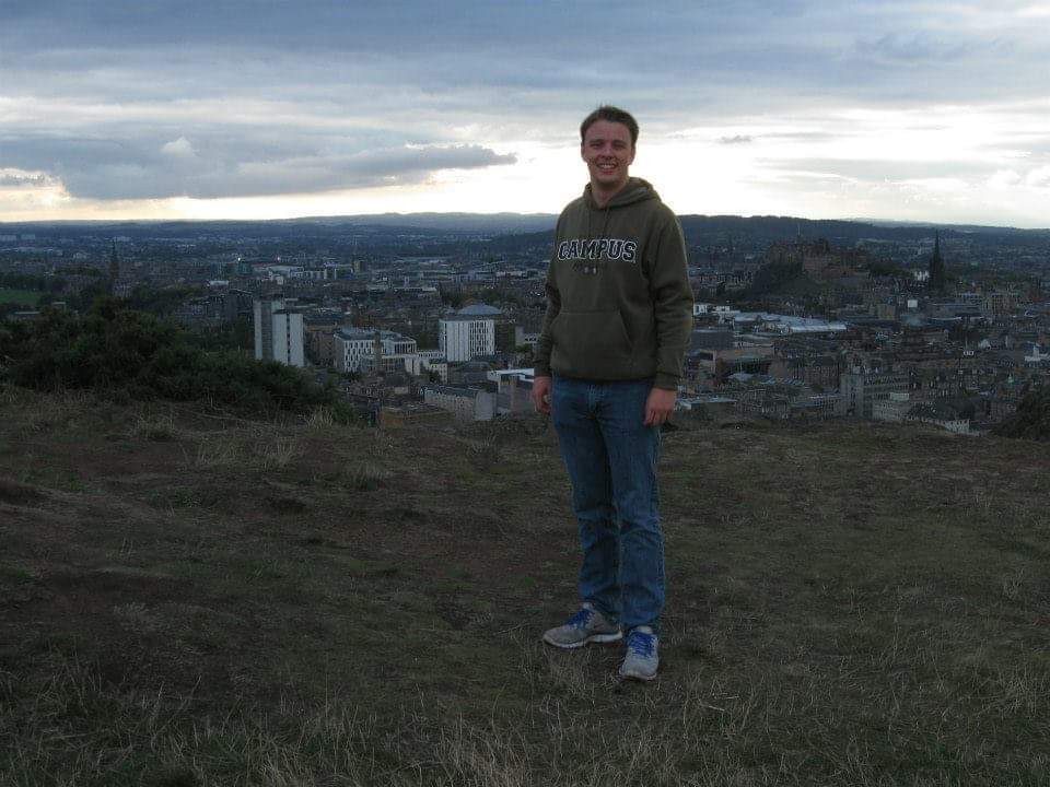 Ryan stands on a hill in Scotland overlooking a town.