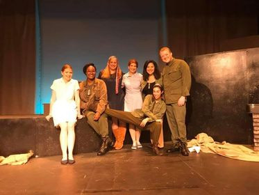 Six women and a man on a theatre set resembling the Vietnam Veterans Memorial wall in Washington D.C. From left to right: Caucasian red headed woman in a white nurse's uniform. Caucasian African American woman in Army fatigues. Caucasian blonde woman in dark blue 1960's folk singer costume. Caucasian red headed woman in light blue red cross uniform. African American woman in Army fatigues. Caucasian blonde man in Army fatigues. In front of them is a black haired caucasian woman in Army fatigues with her leg stretched out. All are smiling