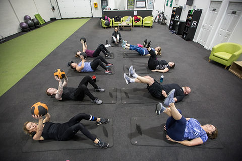 A mixed ability group performing ab exercises on mats during a fitness class