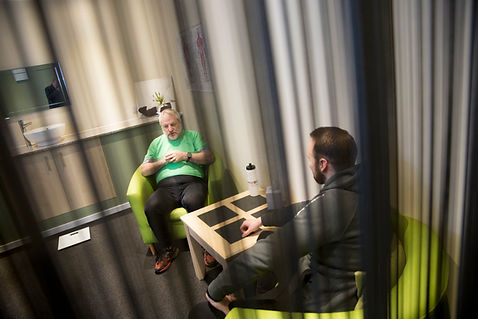 Two men sat on chairs having a health and fitness consultation