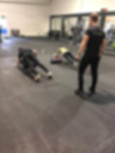 Male personal trainer watching over a couple who are exercisng together